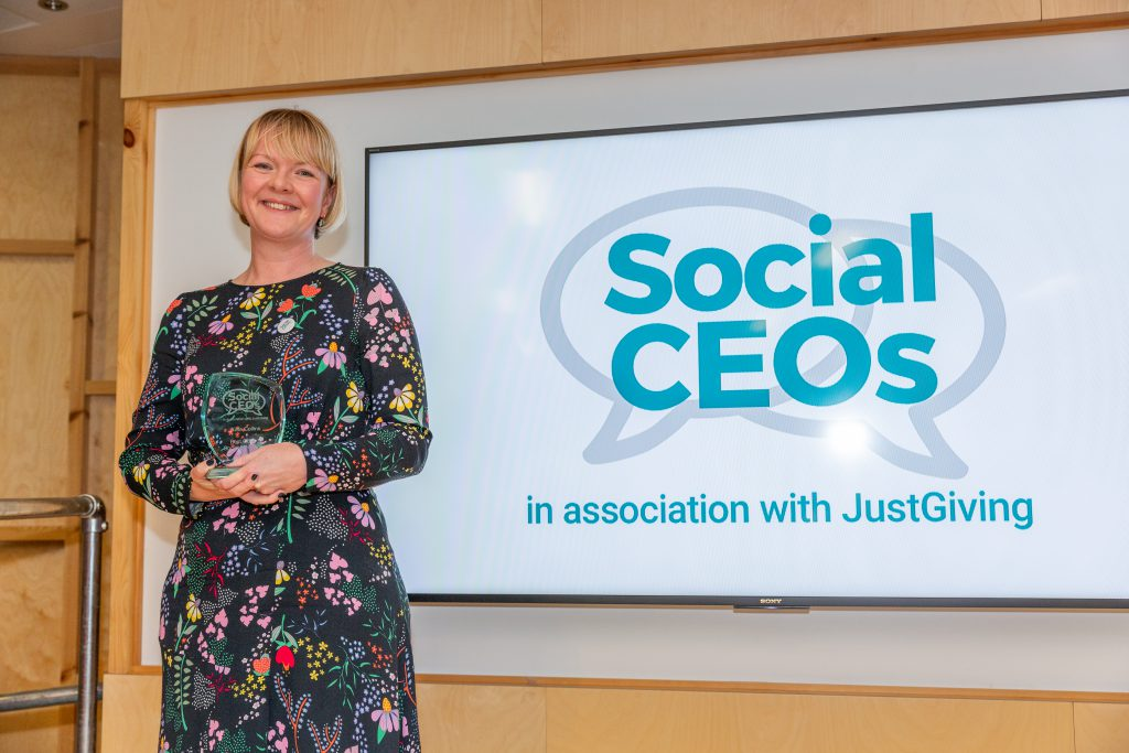 Kate Collins smiling holding her award
